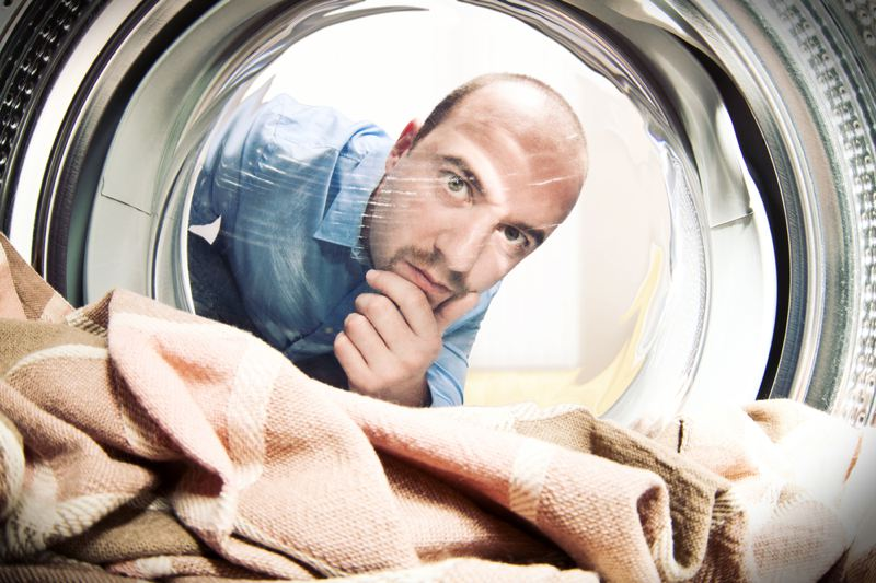 Man looking into washing machine