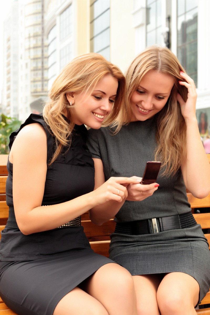 Two smiling girls watching something in mobile phone